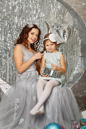 Mother and daughter are waiting for Christmas. Mom dressed fairy fairy plait braids her daughter. Girl holding a gift. Happy parenting and childhood. Family holidays.