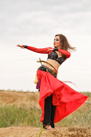 tribal dance: Oriental Beauty dance with a sword. Tribal style. Lovely girl in costume dancing outdoors. Nomads. Passionate dance.