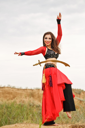 Oriental Beauty dance with a sword. Tribal style. Nice girl in national dress dancing in the open air. Nomads. Stock Photo