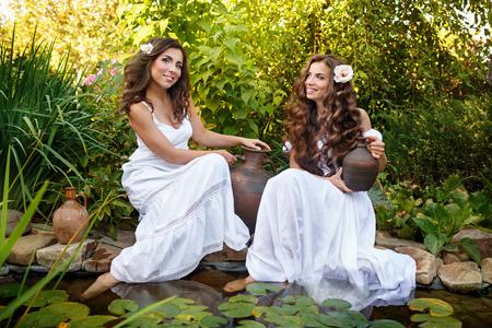 ollas de barro: Dos hermanas vestidas de blanco en el estanque con nenúfares. Las mujeres sacan agua en vasijas de barro pequeñas.