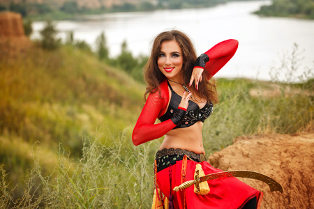 bailarinas arabes: Oriental Beauty dance with a sword. Tribal style. Nice girl in national dress dancing in the open air. Nomads. Sword on her leg the girl