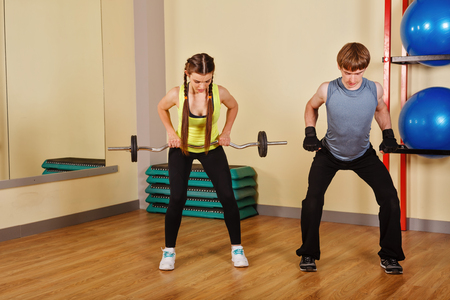 explains: Coach man explains the exercises with barbell for a girl. Personal coach. Healthy lifestyle concept. Fitness.