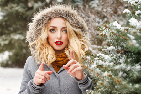 Cute girl in a fur hood standing next to a tree in snow. Walking in a winter park. Close-up portrait. Sexy red lips.