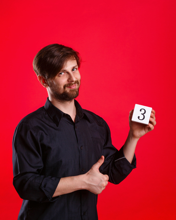 alright: Man holding a cube with the number three. Numerals. Man showing thumb up. Everything gonna be alright.