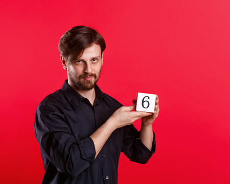 Man holding a cube with the number six. Numerals. A man shows a cube with the number six