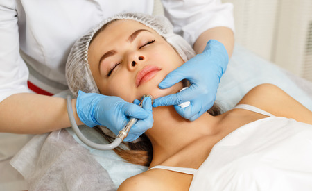 Dermabrasion girl chin. Hardware cosmetology. Spa. Facial Rejuvenation. Mechanical peeling skin.