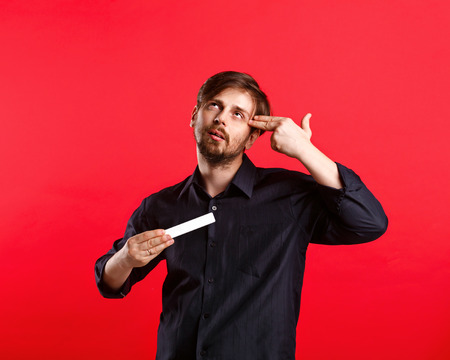 holding gun to head: Man holding an empty copyspace. Advertising Space. An attractive man and holding a sign with both hands. He put two fingers to his head depicting gun.