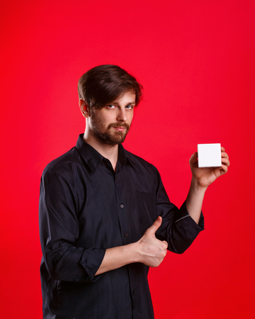 alright: Man holding an empty cube. Advertising Space. Attractive man shows space for copy. Thumb up. Everything gonna be alright. Stock Photo