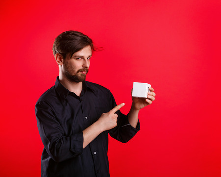forefinger: Man holding an empty cube. Advertising Space. Attractive man shows space for copy. Forefinger. Tricky glance