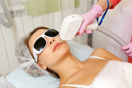 Laser hair removal on the face of a young girl. Machine cosmetology. Cosmetic procedures. Spa. Removing hair from the upper lip.