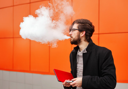 Young hipster man with a beard and glasses smokes an electronic cigarette. He holds a tablet pc. Youth fashion. Delicious pairs.