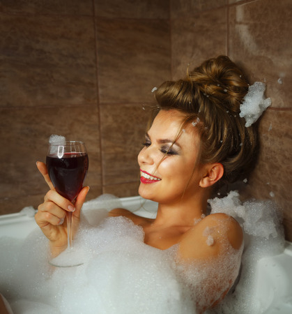 douche: Young cute girl drinking red wine in bath with foam. She relaxes after a hard day. The girl laughs Stock Photo