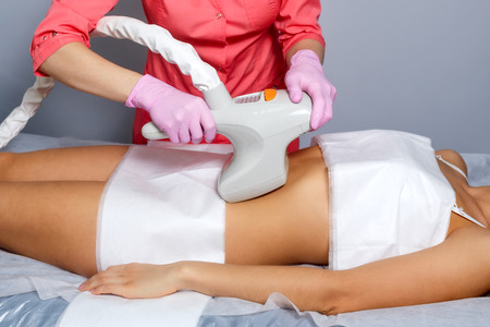 lymphatic drainage therapy: Vacuum massage of the abdomen of a young girl. Instrumental cosmetology. Spa Studio. Rejuvenation and skin tightening. Postnatal stretch marks. Stock Photo