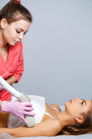 lymphatic drainage therapy: Vacuum massage biceps of a young girl. Apparatus cosmetology. Spa Studio. Rejuvenation and skin tightening. Stock Photo