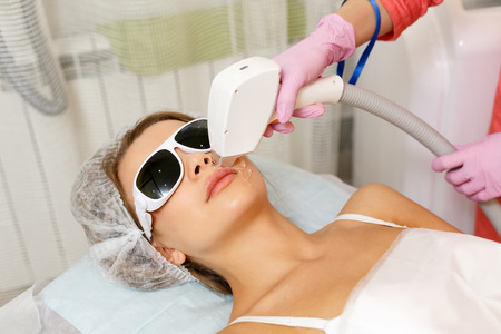 Laser hair removal on the face of a young girl. Hardware cosmetology. Cosmetic procedures. Spa. Removing hair from the upper lip.