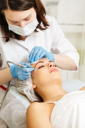 Dermabrasion temples girl. Hardware cosmetology. Spa. Facial Rejuvenation. Mechanical peeling skin. Stock Photo