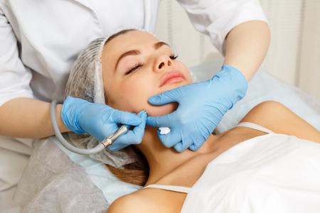Dermabrasion niña de los pómulos. Cosmetología instrumental. Spa. Rejuvenecimiento Facial. Peeling mecánico de la piel.