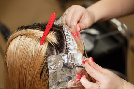 Professional hairdresser holds clients hair coloring. Lightening of the roots of hair. Beauty saloon.