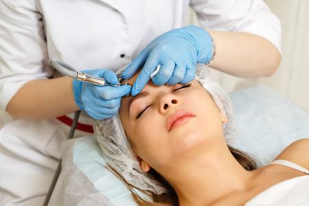 Dermabrasion girls forehead. Apparatus cosmetology. Spa. Facial Rejuvenation. Mechanical peeling skin. Stock Photo