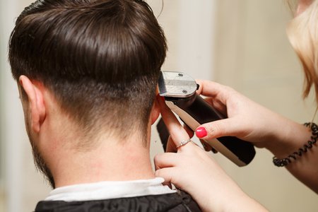 shearer: Professional hairdresser doing haircut mens hair. Cutting electric razor. Beauty saloon. Male beauty. The client is a hipster.