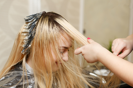 Professional hairdresser holds clients hair coloring. Bleaching the hair roots. Beauty saloon.