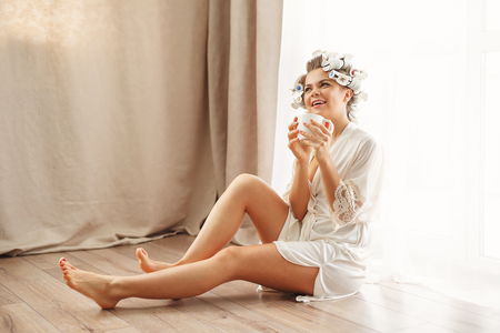 Young attractive housewife sitting on the floor near the window. Girl in a bathrobe and curlers drinking morning coffee. Good morning. She holds a mug with a hot drink.