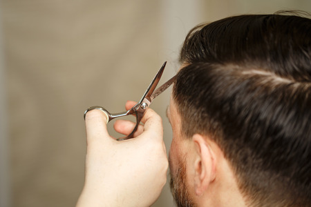 Professional hairdresser doing haircut mens hair. Haircut with scissors. Beauty saloon. Male beauty. The client is a hipster.
