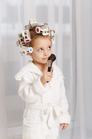 Little girl fashionista. Girl in curlers and a robe holding a makeup brush. Little coquette makes up. Human emotions.