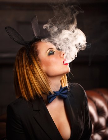 Young attractive girl in a jacket, a butterfly tie and bunny ears smokes an electronic cigarette. Femme fatale. Evening makeup smokey eye. She lets out thick steam from her mouth. Pleasure in vice.