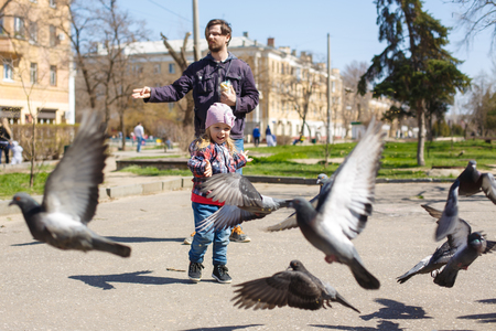 Father and daughter on a walk are fed in a park of pigeons. Caring for animals. Pigeons frantically scattered on their own.