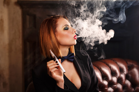 Young attractive girl in a jacket and bow tie smokes electronic cigarette. Femme fatale. Evening makeup smokey eye. She lets out a thick steam from her mouth Stock Photo