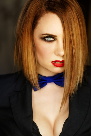 Young attractive girl in a jacket and bow tie looks languidly. Femme fatale. Evening makeup smokey eye. Expressive eyes.
