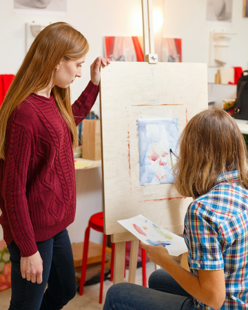 Classes in art school. The teacher observes the student. Girl draws still life with watercolors. Courses of drawing for adults.