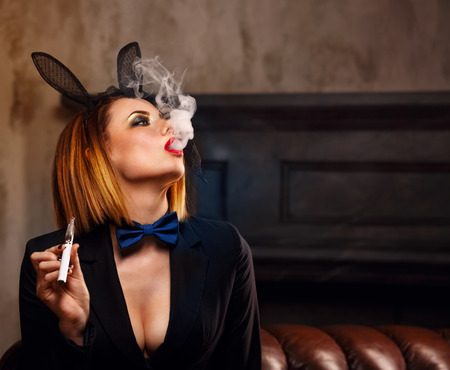 Young attractive girl in a jacket, a butterfly tie and bunny ears smokes an electronic cigarette. Femme fatale. Evening makeup smokey eye. She lets out a thick steam from her mouth. Pleasure in vice.