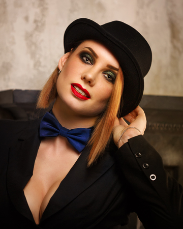 femme fatale: Young attractive girl in a jacket, bow tie and bowler hat. Femme fatale. Evening makeup smokey eye. Stock Photo