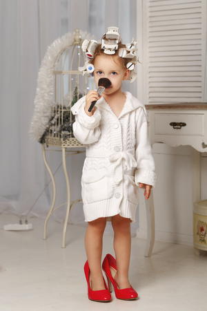Little girl fashionista. A girl in a curler, a robe and red high-heeled shoes is holding a makeup brush. Little coquette. Human emotions. Stock Photo
