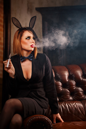 A young attractive girl in a jacket, a butterfly tie and bunny ears smokes an electronic cigarette. Femme fatale. Evening makeup smokey eye. She lets out a thick steam from her mouth