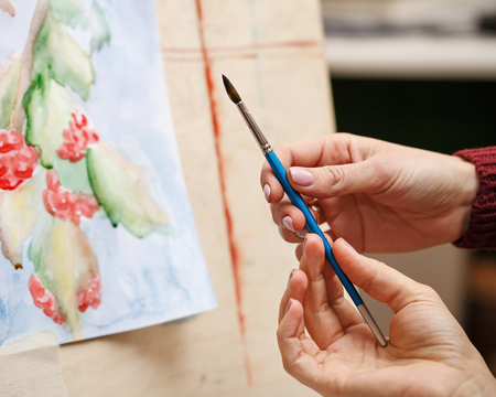 Girl paints still life in watercolor art school. The teacher helps to correct the defects in the picture. Hands close-up. Courses of drawing for adults. Reklamní fotografie