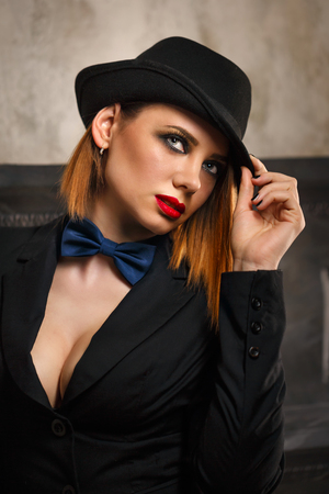 femme fatale: Young attractive girl in a jacket, bow tie and bowler hat. Femme fatale. Evening makeup smokey eye. She looks past.