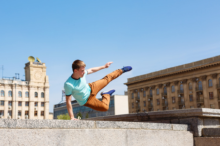 Young man jumps over the wall. Parkour in the urban space. Sport in the city. Sport activity. Stock Photo