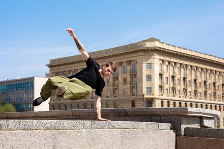 若い男が壁を飛び越えます。都市空間におけるパルクール。市内のスポーツ。スポーツ活動。 写真素材