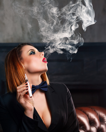 femme fatale: Young attractive girl in a jacket and bow tie smokes electronic cigarette. Femme fatale. Evening makeup smokey eye. Delicious steam.