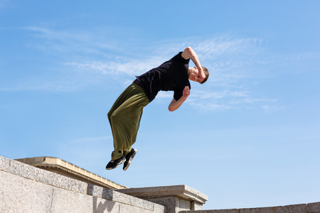 Young man doing a back flip with a turn. Parkour in the urban space. Sports in the city. Sport activity.