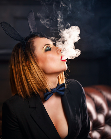 Young attractive girl in a jacket, a butterfly tie and bunny ears smokes an e-cigarette. Femme fatale. Evening makeup smokey eye. She lets out a thick steam from her mouth. Pleasure in vice.