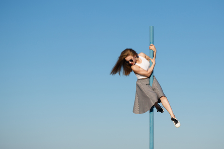 Young attractive girl hipster dancing on the pole. She is wearing a top, a skirt and sunglasses. Flying hair. The concept of life in motion.