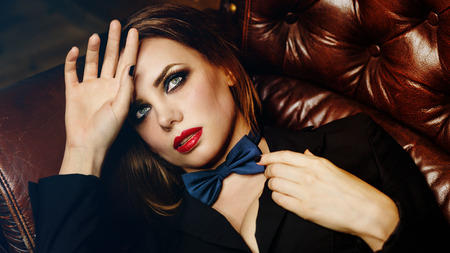 Young attractive girl in a jacket and bow tie. Femme fatale. Evening makeup smokey eye. She lies on the leather couch and is sad.