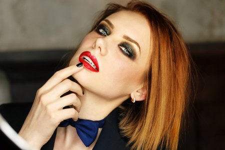 Young attractive girl in a jacket and bow tie looks languidly. Femme fatale. Evening makeup smokey eye. Lust.