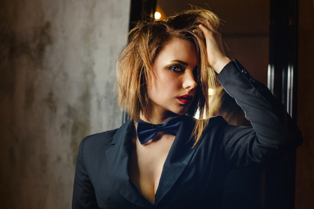 Young attractive girl in a jacket and bow tie. Femme fatale. Evening makeup smokey eye. She straightens her hair. Passion and desire. A languid look Stock Photo