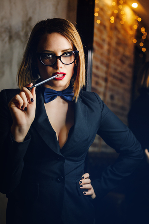 femme fatale: Young attractive girl in a jacket, bow tie and glasses. Femme fatale. Evening makeup smokey eye. She lustfully bites the pen. Stock Photo
