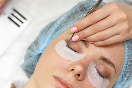 Beauty salon. The procedure of fastening the extended eyelashes. Shooting close-up. Aesthetic facial treatment. Expressive look.